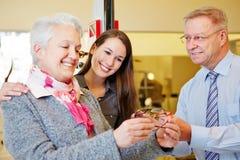 年长妇女买的玻璃 库存图片