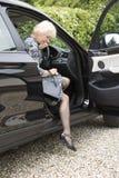 年长妇女司机和提包离开汽车 免版税库存图片