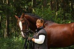 年长妇女和棕色马画象在森林里 库存图片