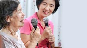 年长妇女在家唱与女儿的一首歌曲 免版税图库摄影