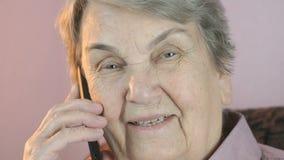 年长妇女在有微笑的智能手机谈话 股票录像