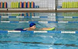 年长妇女在被盖的公开游泳池游泳。 免版税库存照片