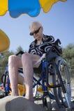年长妇女在轮椅坐海滩 免版税图库摄影