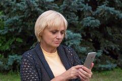 年长妇女拨号盘或文本在手机 免版税库存图片