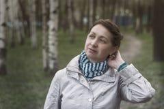 年长妇女是在桦树之间的操作公园,剧烈的设计 免版税库存照片