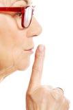 年长妇女有在她的嘴唇的手指。外形。 免版税库存图片