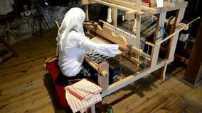 年长妇女生产在手摇纺织机的布料 股票录像