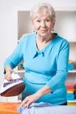 年长妇女电烙的衬衣 库存照片