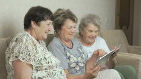 年长妇女看在片剂屏幕上的照片  影视素材