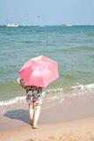 年长妇女穿戴了简而言之与站立在海滩沙子的一把桃红色伞的 免版税库存照片