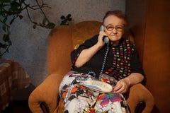 年长妇女谈话在家庭电话 免版税图库摄影