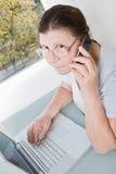 年长妇女谈话在手机,当工作在compu时 库存图片