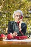 年长妇女谈话在电话在后院 免版税库存照片