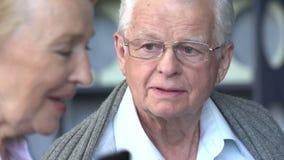 年长妇女谈话在电话以她的丈夫为背景 股票视频