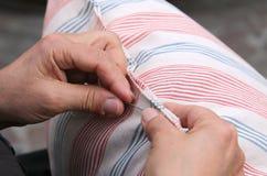 年长妇女,当缝合与针时和穿线枕头 免版税库存图片