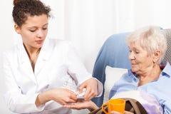 给年长妇女维生素的家庭护士 免版税图库摄影