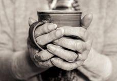 年长妇女` s递拿着一份热的饮料 单色 图库摄影