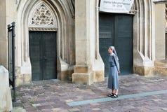 年长尼姑看见在宽容大教堂的墙壁上的广告 库存图片