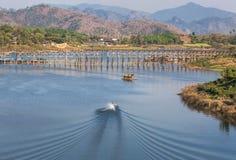 长尾巴在songkhalia河的小船航行kanchanaburi的,泰国有最长的老木桥背景 免版税库存图片