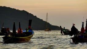 长尾巴小船在有太阳的金黄光的安达曼海转换了在日落和小船背景前 影视素材