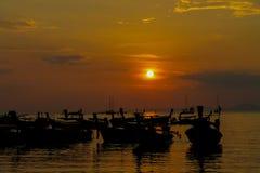 长尾巴小船日落剪影在海海湾的在泰国 免版税图库摄影