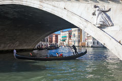 长平底船在Rialto桥梁下在威尼斯意大利 免版税库存照片
