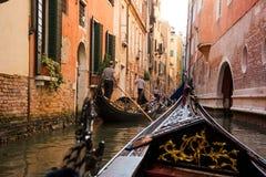 长平底船的前面部分在威尼斯桥梁下  驾驶长平底船的平底船的船夫 免版税库存照片