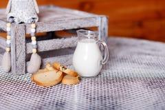长方形宝石和牛奶在一个水罐在桌上 免版税库存图片