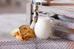 长方形宝石和牛奶在一个水罐在桌上 免版税库存照片