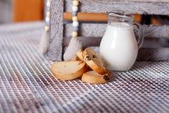 长方形宝石和牛奶在一个水罐在桌上 免版税图库摄影