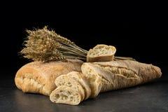 长方形宝石和ciabatta,在黑暗的木桌上的面包切片 麦子和新鲜的混杂的面包在黑背景 免版税库存照片