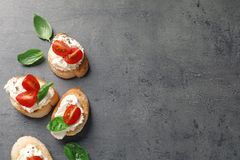 长方形宝石片断与鲜美奶油奶酪和蕃茄的在灰色桌,平的位置上 库存照片