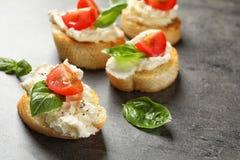 长方形宝石片断与鲜美奶油奶酪和蕃茄的 库存照片