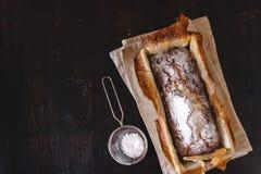 长方形资本杯形蛋糕用在一个金属烘烤盘的糖粉在黑暗的背景 r o r 库存图片