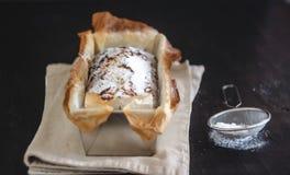 长方形资本杯形蛋糕用在一个金属烘烤盘的糖粉在黑暗的背景 r o r 库存照片