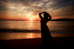长期亭亭玉立的女孩剪影反对在海的日出 免版税库存照片