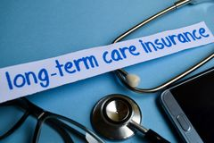 长期护理保险题字有听诊器、镜片和智能手机看法在蓝色背景 免版税库存照片