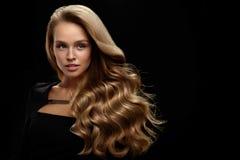 长期美丽的头发 与白肤金发的卷发的妇女模型 免版税库存照片
