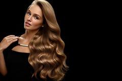长期美丽的头发 与白肤金发的卷发的妇女模型 免版税库存图片