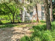 长木凳和开花树在城市在居民住房附近停放 儿童比赛的` s操场 免版税库存图片