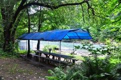 长木凳和桌在一条山河的河岸在机盖下 免版税库存图片