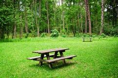 长木凳和桌在森林里 免版税库存照片