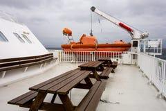 长木凳和橙色救生艇在一条白色轮渡的甲板 免版税库存照片