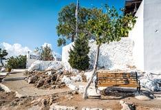 长木凳和绿色树在Tsampika教会附近墙壁罗得岛海岛的,希腊 免版税库存照片