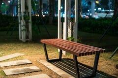 长木凳在公园在晚上 免版税库存照片