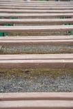 长木凳行的背景在街道上的在夏天 免版税库存照片