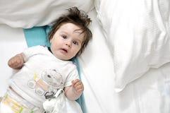 长毛的婴孩在与二个枕头的河床上 免版税库存照片