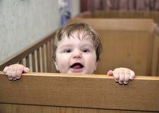 长毛的婴孩在河床倾斜并且微笑 免版税库存照片