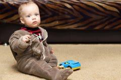 长毛绒衣服的逗人喜爱的男婴坐地板 库存照片