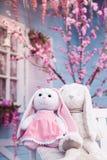 长毛绒兔宝宝坐白色长木凳在开花的樱花和蓝色背景 免版税库存照片